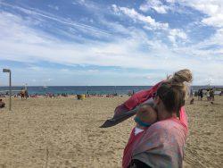 Koala and Mama Babywearing Malta wrapping on the beach with oscha andaluz allegro woven wrap